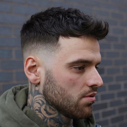 a French crop with spiky fringe delivers a rugged finished look and a beard adds to it
