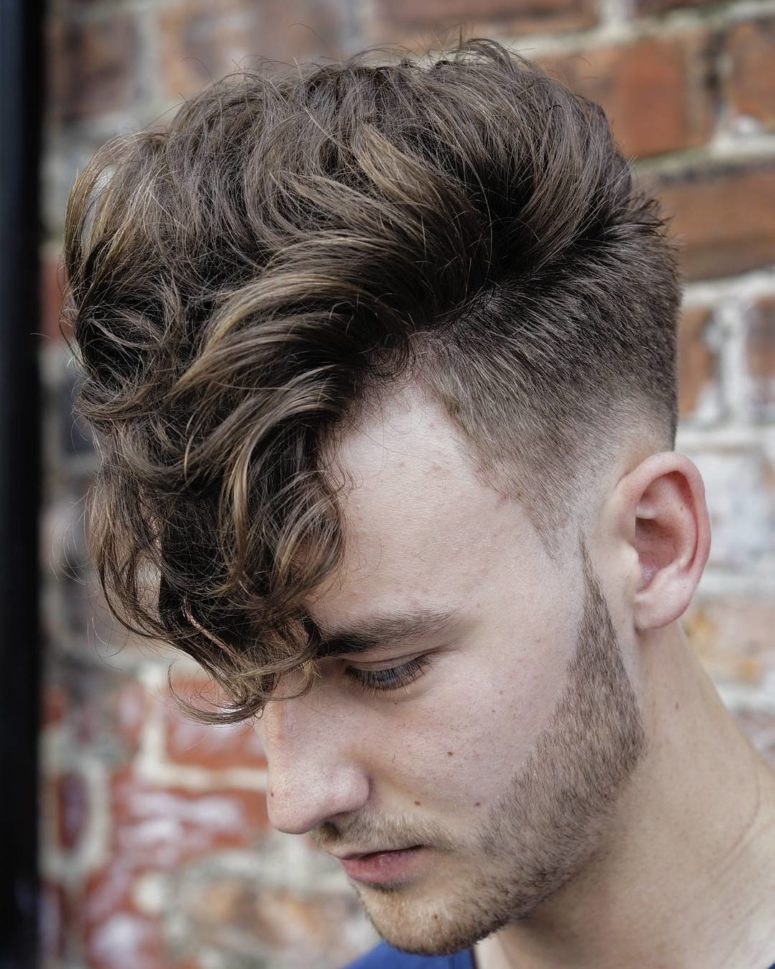 a long curly fringe and a low skin fade haircut is a stylish and bold idea