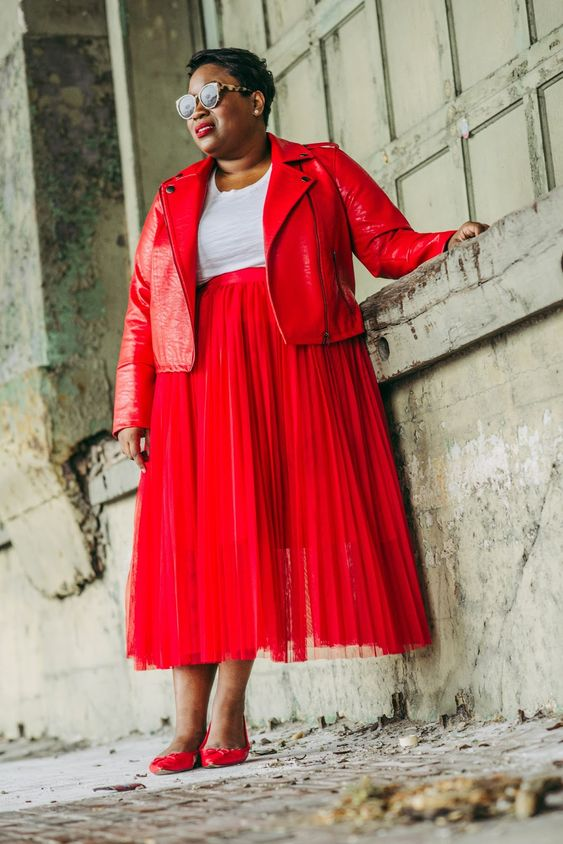 a red leather jacket, a red pleated midi skirt, a white tee, red bow flats