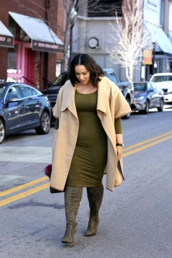 an olive green knee dress with long sleeves, green tall boots, a neutral sleeveless coat and a fuchsia bag