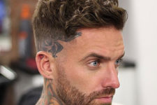 05 a short wavy side swept haircut with shaved sides and a beard looks hot and edgy