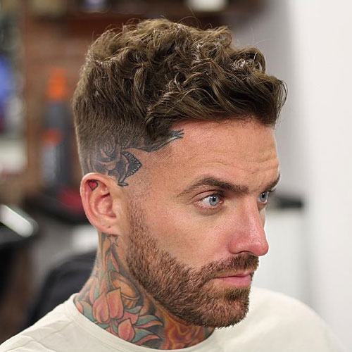 a short wavy side swept haircut with shaved sides and a beard looks hot and edgy