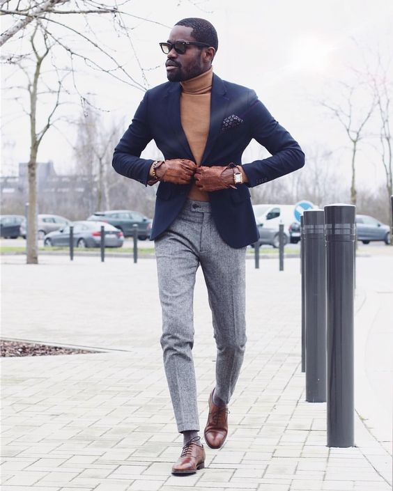 an elegant groom's outfit with grey pants, a mustard turtleneck, a navy blazer and brown shoes