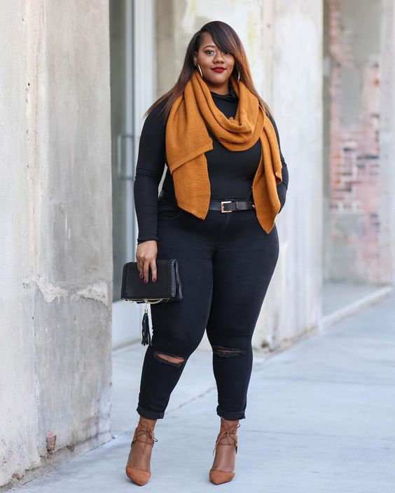 black ripped skinnies, a black turtleneck, a rust scarf and rust lace up shoes plus a black clutch