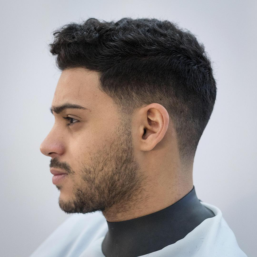 a low fade haircut is a stylish idea to rock naturlaly curly hair
