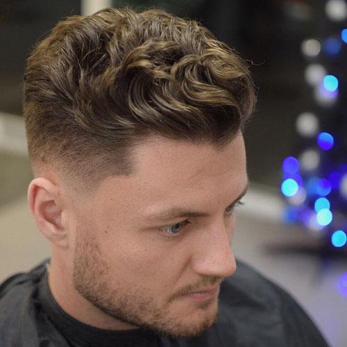a low skin fade and a short wavy slick back is a great modern look for both thin and thick hair