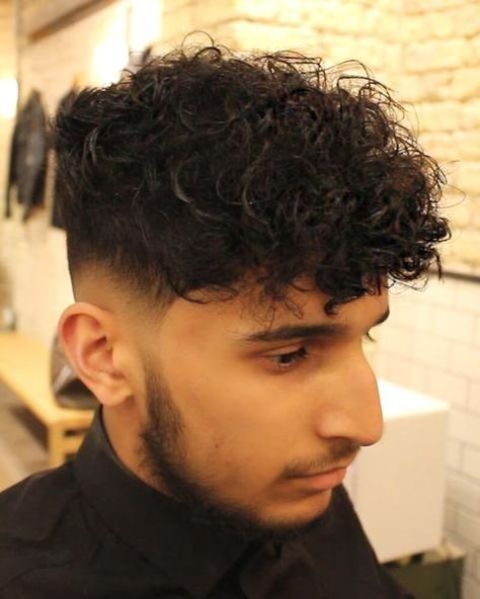 a low skin fade curly haircut with a disconnected undercut is a stylish ide