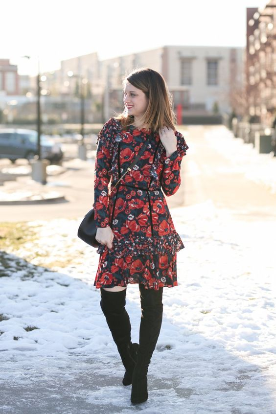 a red floral knee dress with black tall boots and a black bag for a feminine feel