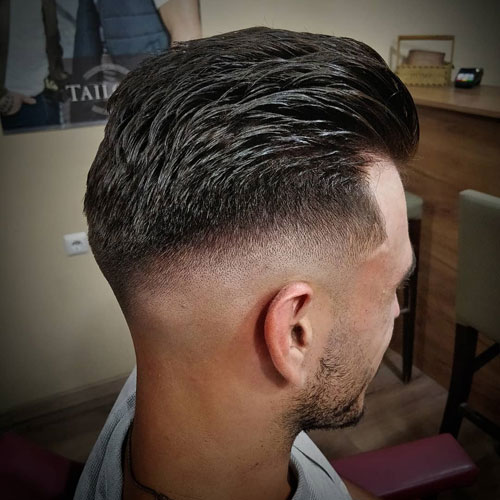 such a mid top fade haircut looks flawless with thick brush back hair and a cool edge