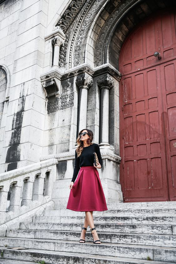 a black long sleeve top, a deep berry hued midi skirt and black ankle strap shoes