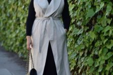 08 a black long sleeve top, black leggings, black heels, a neutral sleeveless coat and a black bag