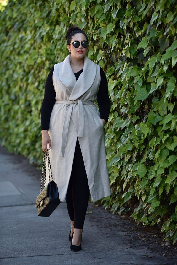 a black long sleeve top, black leggings, black heels, a neutral sleeveless coat and a black bag
