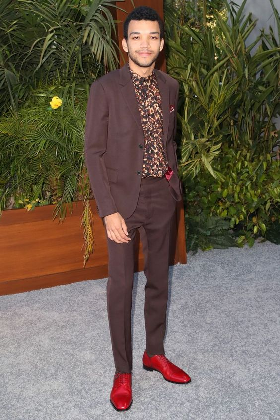 a dapper look with a chocolate brown suit, red shoes and a printed shirt for a more formal date