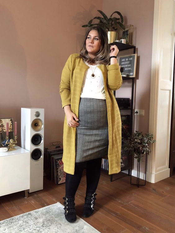 a grey plaid knee skirt, a white pearl top, a long mustard cardigna, black tights and booties