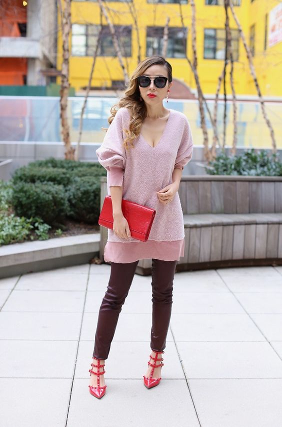 a casual look with a long pink sweater, chocolate colored leather pants, red spiked shoes and a red clutch