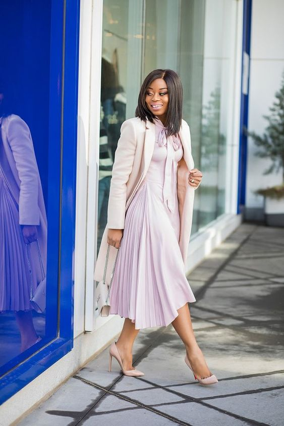 a chic light pink dress with a high neckline and a pleated skirt, blush heels and a creamy coat