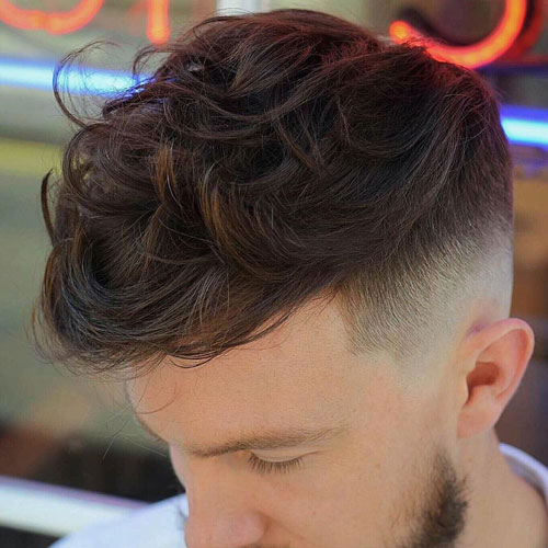 a textured wavy quiff and a fade is one of the hottest haircuts to rock right now
