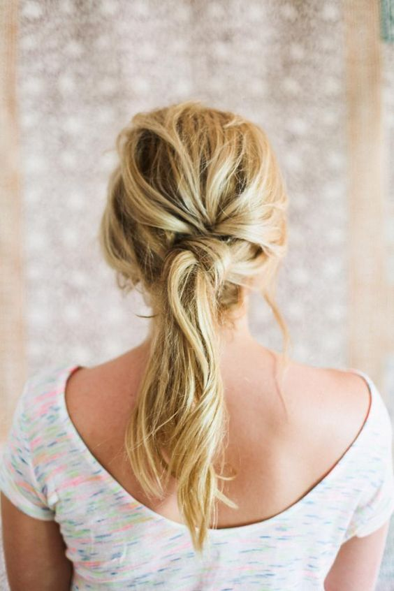 a fashionable twisted and messy ponytail with a messy bump for a relaxed feel