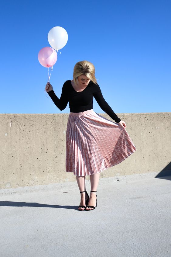 a simple monochromatic look in pink and black, with a pleated midi and black heels