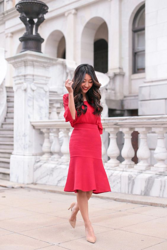 a cool red outfit with a fit and flare skirt, a red long sleeve top and nude heels