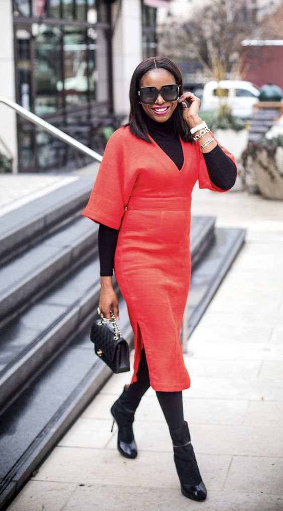 a red midi dress worn with a black turtleneck, black tights, boots and a black bag
