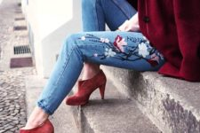 13 a pink shirt, blue jeans with floral embroidery, red booties and a burgundy coat