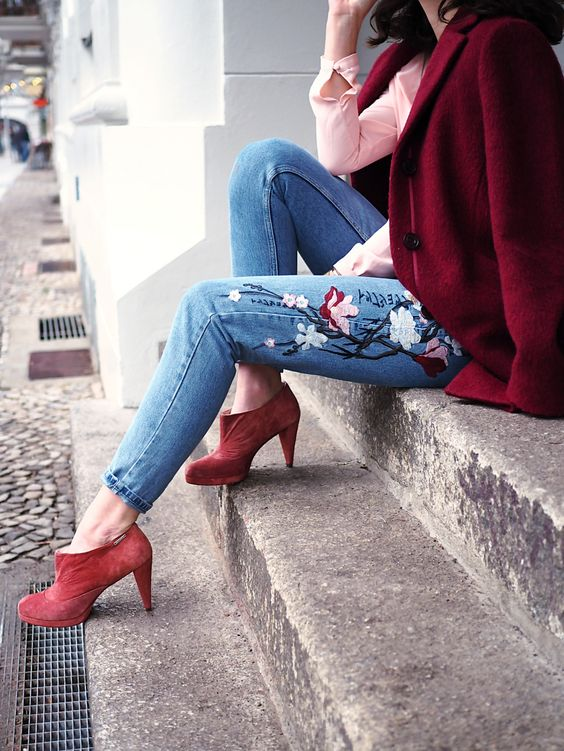 a pink shirt, blue jeans with floral embroidery, red booties and a burgundy coat