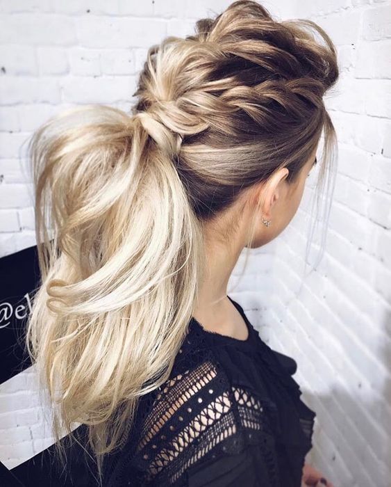 a voluminous high ponytail with several braids on top and with wavy textural hair