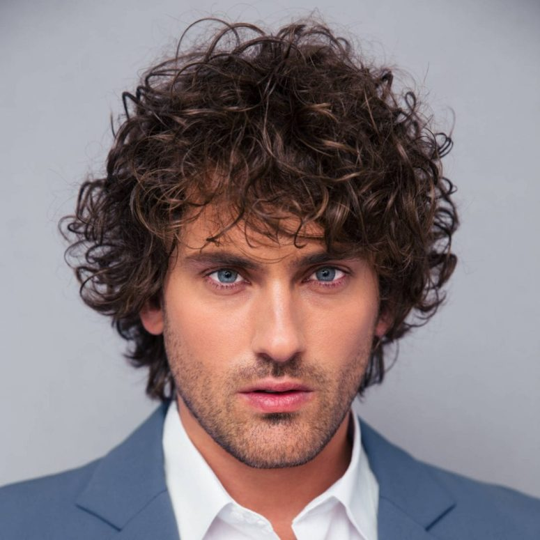 curls take center stage in this haircut flowing downward to give this style a sense of motion