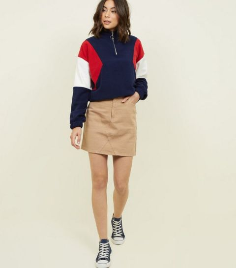 With beige skirt and sneakers