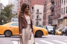 With beige top, brown jacket, high heels and beige bag