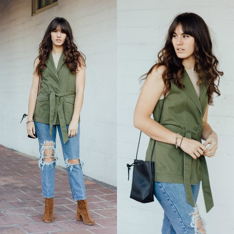With beige top, distressed jeans, black small bag and brown suede boots