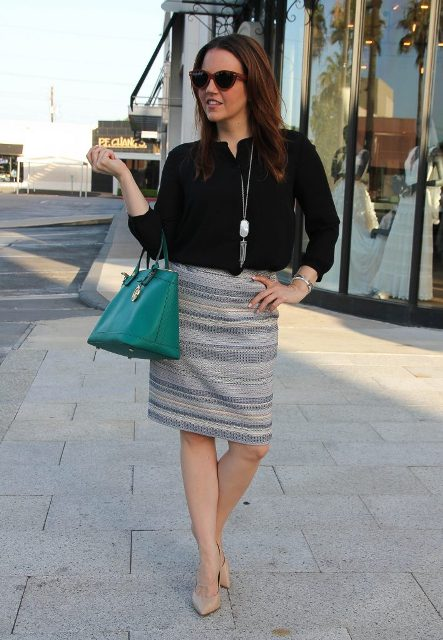 With black blouse, emerald bag and beige pumps