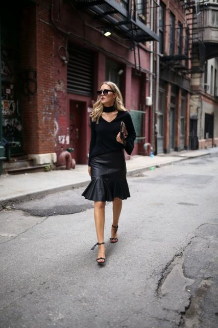 With black leather skirt, high heels, clutch and sunglasses