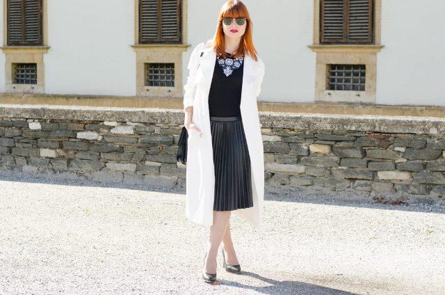 With black shirt, white coat, black pumps and black bag