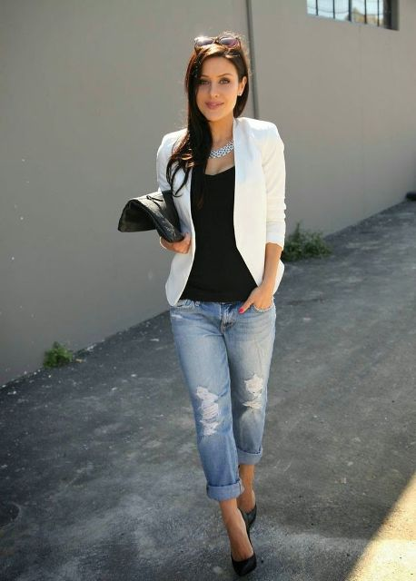 With black top, distressed jeans, black pumps and black clutch