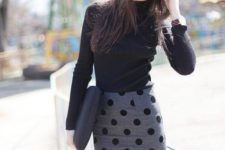 With black turtleneck and clutch
