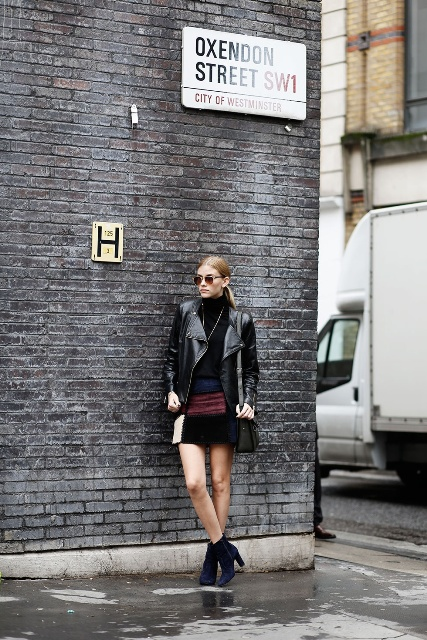 With black turtleneck, black leather jacket, ankle boots and bag