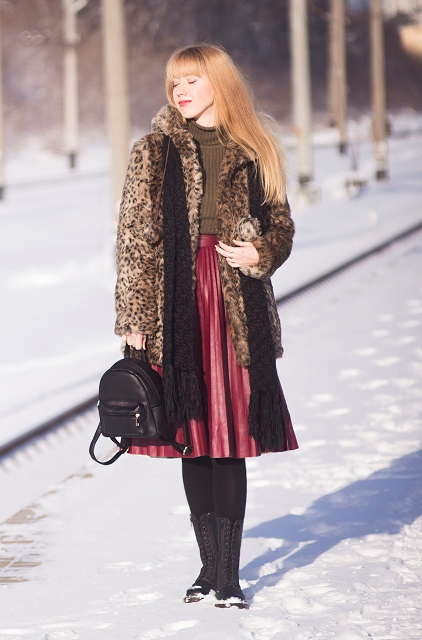 With brown turtleneck, leopard coat, black backpack, black scarf and lace up boots