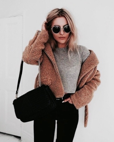 With gray crop shirt, black pants and black chain strap bag