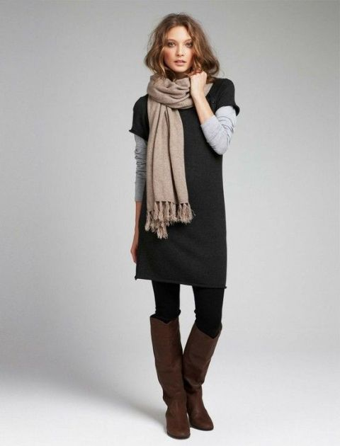 With gray shirt, beige scarf, black tights and brown leather high boots