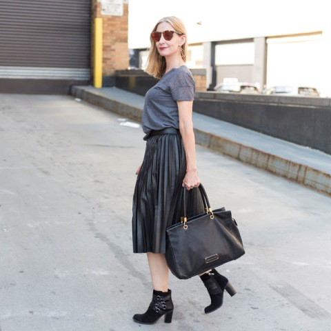 With gray shirt, black ankle boots and black tote bag