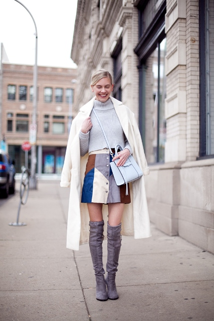 With gray sweater, white coat, light blue bag and gray boots