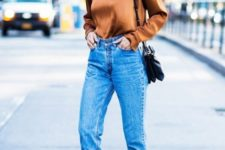 With high-waisted jeans, black bag and printed shoes