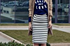 With labeled t-shirt, beige trench coat and blue pumps