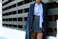 With light blue shirt, navy blue coat, flat shoes and black mini bag