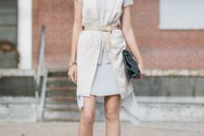 With light gray dress, black cutout boots and clutch