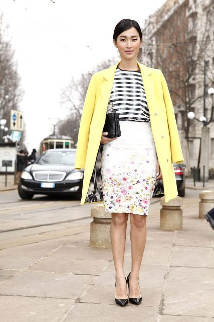 With striped shirt, yellow coat, black shoes and clutch