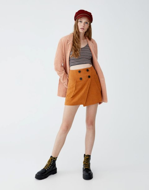 With striped top, peach cardigan, lace up boots and cap