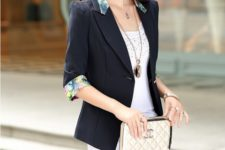 With top, white pants and beige clutch